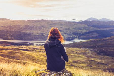 Photo for Woman looking at the sunset over mountains - Royalty Free Image