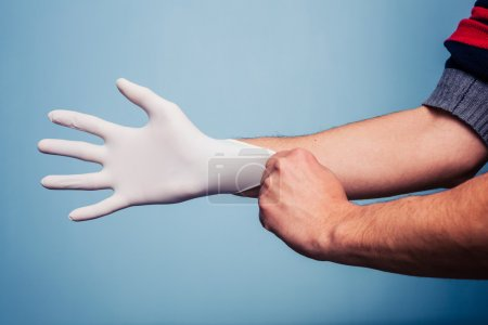 Man putting on latex surgical glove
