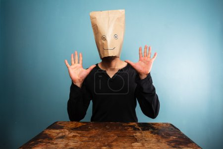 Stupid man with bag over his head and hands up...