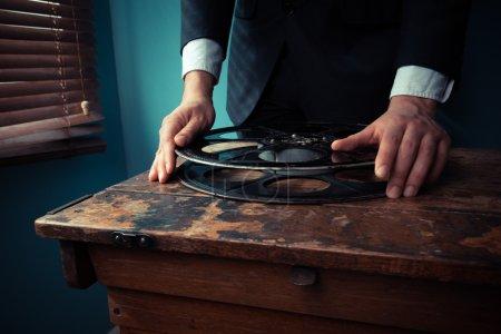 Photo pour Producteur de cinéma gère une bobine de film dans une salle de projection de la fenêtre - image libre de droit