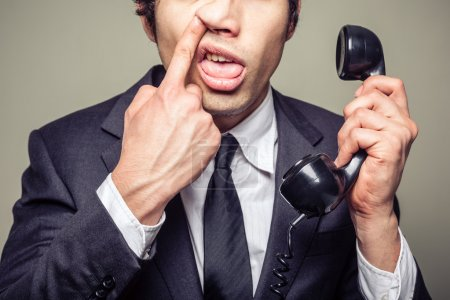 Photo pour Jeune entrepreneur incompétent est au téléphone et se redresse son nez - image libre de droit