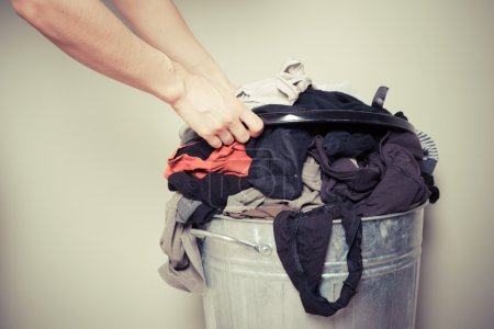 Photo for Young woman is sorting out her laundry at home - Royalty Free Image
