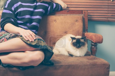 Photo pour A young woman is sitting on a sofa with her cat - image libre de droit