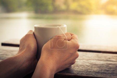 Photo pour Gros plan sur les mains d'une femme tenant une tasse de thé près d'un lac dans l'après-midi - image libre de droit