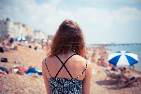 Photo for A young woman is on the beach looking at people sunbathing and relaxing - Royalty Free Image
