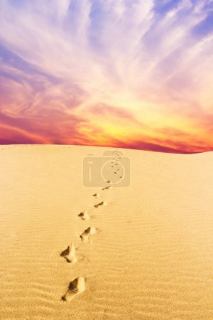 Footprints on desert and Purple and pink clouds in...