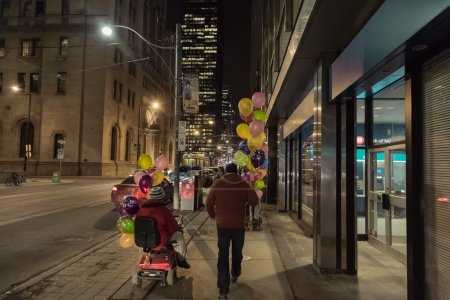 Husband and wife in motorized car promenade on Toronto downtown night streets and celebrate her birthday
