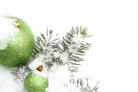 Two green christmas balls with snow covered pine tree
