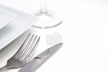 Dinner place setting. white square china plates with silver cutlery and glass