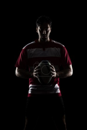 Rugby player in a red uniform. Black Background...