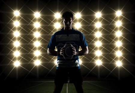 Rugby player silhouette in front of lights in a bl...