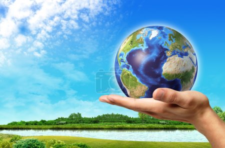 Photo for Man hand with earth globe on it and a beautiful green landscape with river and blue sky, on background. - Royalty Free Image