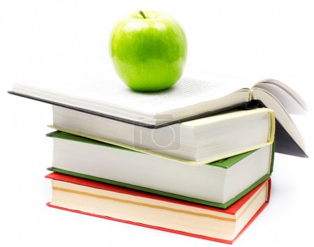 Stack of open books with green apple on white background.