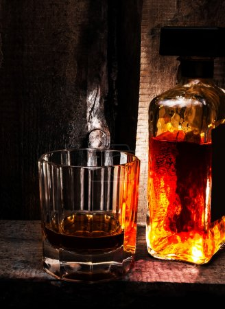 Photo for Glass of Whisky Scotch and a bottle on old wooden background. Old vintage dark oak countertop and glass of hard alcohol. - Royalty Free Image