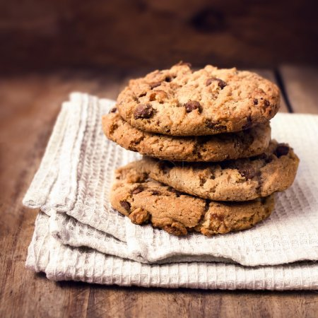 Photo for Stacked chocolate chip cookies on white napkin in country style. Chocolate chip cookies shot on wooden table with selective focus. - Royalty Free Image