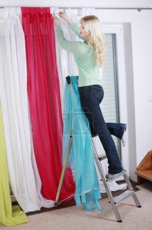 Photo pour Femme sur une échelle raccroche les rideaux chez elle - image libre de droit