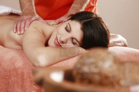 Photo pour Femme allongée sur un banc de massage se faisant masser - image libre de droit