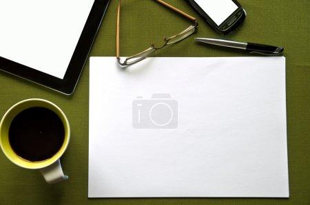 Photo pour Bureau vert avec café, tablette, lunettes, téléphone, stylo et un papier blanc - image libre de droit