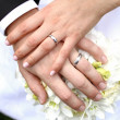 Hands with rings on flower during wedding...