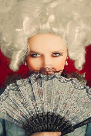 Photo pour Retrato de estilo barroco de una bella mujer joven detrás de un ventilador de mano - image libre de droit