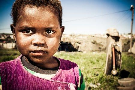 Photo pour Petite fille africaine avec de grands yeux sombres jouant à l'extérieur dans le canton - image libre de droit