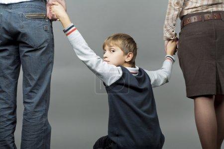 Photo pour Garçon adolescent caucasien avec parents, regarder en arrière avec l'expression du visage anxieuse, tenant par la main des parents isolés sur fond gris - image libre de droit