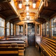 An old tram interior, wooden seats in the garage...