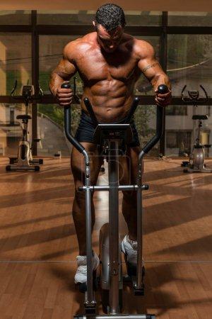 Male bodybuilder using the elliptical machine