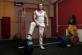 Bodybuilder preparing for deadlift of barbell