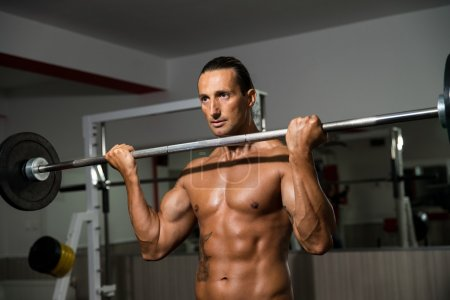 Photo for Men In The Gym Performing Biceps Curls With A Barbell - Royalty Free Image