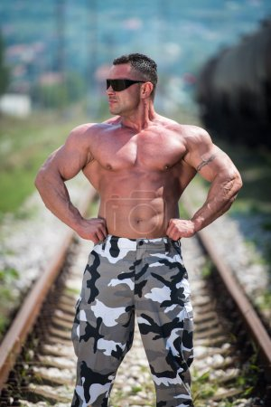 Body Builder Posing At The Railroad