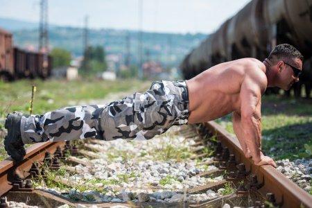 Handsome Man Doing Pushups At Railroad