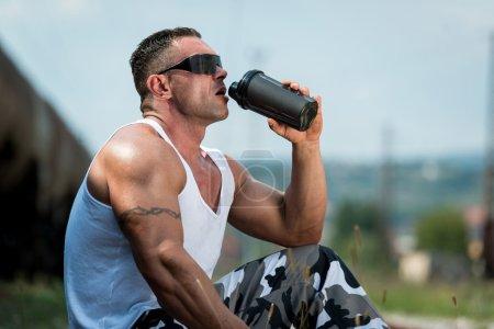 Photo pour L'homme sain au repos et de l'eau potable ou de boisson protéinée au chemin de fer - image libre de droit