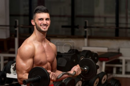 Men In The Gym Performing Biceps Curls With A Barbell