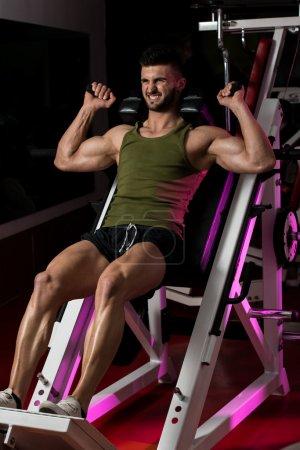 Photo pour Fit l'homme à l'aide de la machine de presse de jambe dans un club de santé - image libre de droit