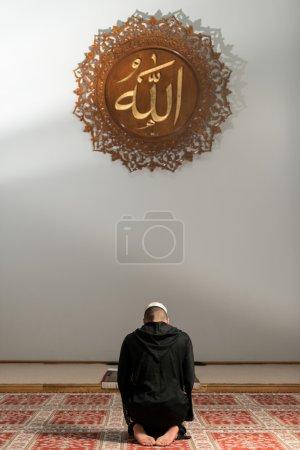 Photo pour Jeune homme musulman faisant la prière traditionnelle à Dieu tout en portant un chapeau traditionnel Dishdasha - image libre de droit