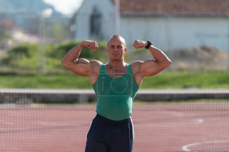 Bodybuilder Performing Front Double Biceps At Tennis Place