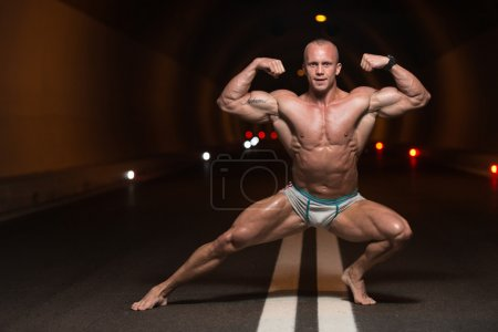 Photo for Bodybuilder Performing Front Double Biceps Poses In Tunnel - Royalty Free Image