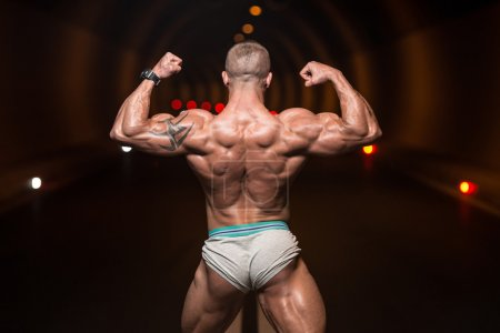 Bodybuilder Performing Rear Double Biceps Poses In Tunnel