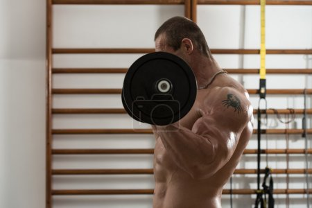 Photo for Healthy Man Working Out Biceps In A Health Club - Royalty Free Image