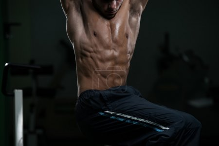 Photo for Young Man Performing Hanging Leg Raises Exercise - One Of The Most Effective Ab Exercises - Royalty Free Image