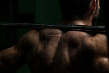 Photo for Young Man Performing Barbell Squats - One Of The Best Body Building Exercise For Legs - Royalty Free Image