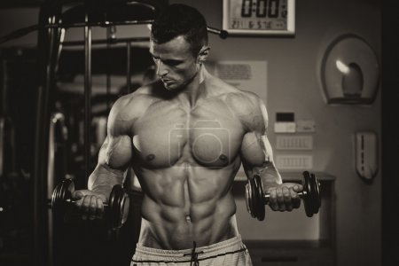 Photo for Young Man Working Out Biceps - Dumbbell Concentration Curls - Royalty Free Image
