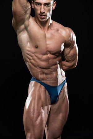 Photo pour Jeune bodybuilder flexion des muscles - Isoler sur Blackground noir - Espace de copie - image libre de droit