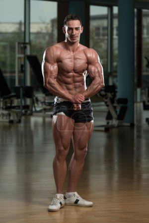 Photo for Serious Men Standing In The Gym And Flexing Muscles - Royalty Free Image