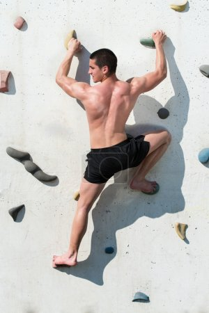 Young Man Hanging From A Climbing Wall