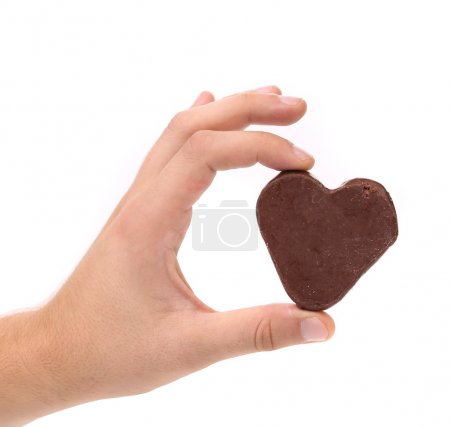 Hand holds chocolate heart shape