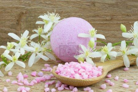 Photo pour Bombe de bain rose et sel de bain sur une cuillère sur un fond en bois - image libre de droit
