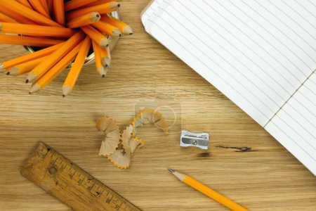 Top-view of pencils, lined paper, ruler and pencil sharpener