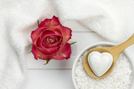 Bath fizzer in heart shape on wooden spoon on top of bowl filled